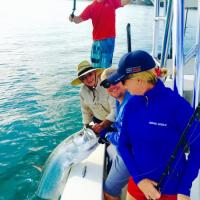 Capt Rich Andretta and crew admiring the beautiful silver king tarpon boatside after a great fight
