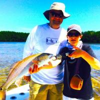 First mate Grady and Client posing with a top slot redfish on this Tampa Fishing Charter