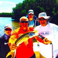 Group effort posing with his healthy snook on a Tampa fishing charter
