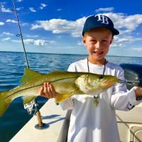 This young man with his first and biggest snook caught during Anna Maria island fishing charter