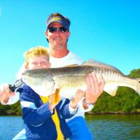 Father/Son dueo with a monster over slot redfish during a Ft. Desoto fishing charter